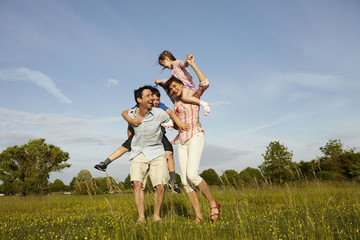 A family, two parents outdoors in the summer giving piggybacks to two children.