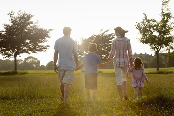 A family, two parents and two children walking hand in hand across grass outdoors in the summer.
