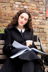 a thoughtful young woman with a coffee and diary