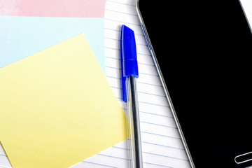 Smartphone, a pen and paper for notes on a notepad