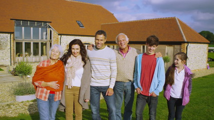 Portrait of happy extended family group standing outside rural home