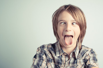 funny boy with cross-eyed and tongue out - vintage style photo