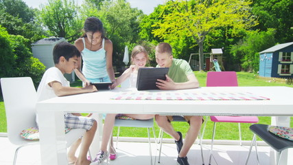 Young friends in the garden on a summer day playing with a computer tablet