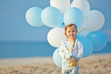 Happy kid play with balloons on the beach