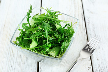 Glass bowl of green salad on wooden background