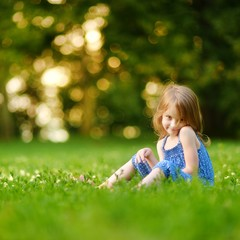 Cute little girl sitting on the grass on summer