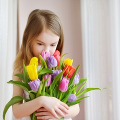 Adorable little girl holding tulips by the window