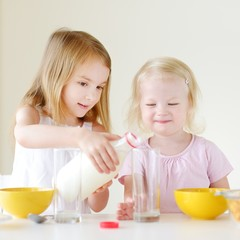 Two cute little sisters eating cereal in a kitchen