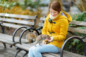 Young beautiful woman feeding a squirrel