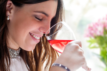 Close up of girl smelling wine.