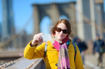Young woman taking a selfie on Brooklyn Bridge