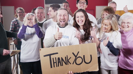 "Group of charity volunteers give thumbs up to camera with a ""Thank You"" sign"