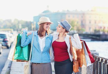 Two happy beautiful girls with shopping bags embrace in the city