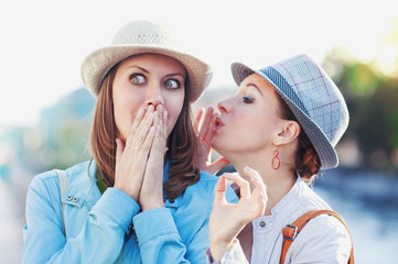 Young beautiful woman telling secret to her friend