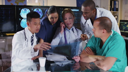 Group of colleagues in a medical meeting discuss a patient's x ray results