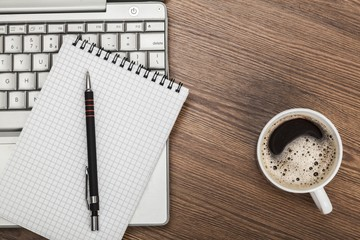 Above. Blank notepad over laptop and coffee cup on office wooden