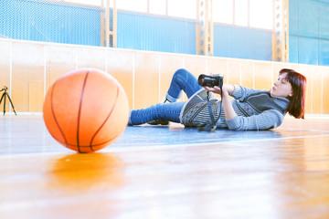 Woman photographs a basketball ball