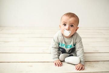 One year old cute baby boy sitting on wooden floor