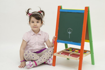 Adorable girl draw a flower on black board with chalk
