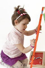 Adorable girl draw on black board with chalk
