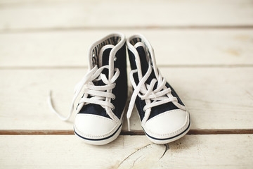 Baby black and white sneakers on wooden floor