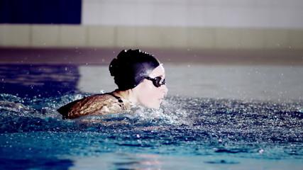 Powerful female swimmer in training doing the butterfly stroke