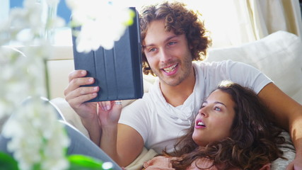 Couple relaxing together at home with a computer tablet.