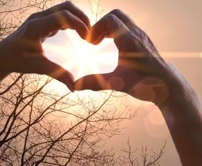 Menschenhände zeigen die Sonne im Herzen