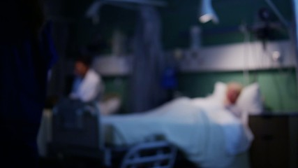 Elderly female patient resting in bed with medical team working in the backgroun