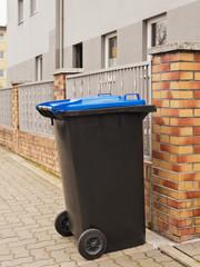 Eine schwarze Mülltonne mit Rädern und einem blauen Deckel