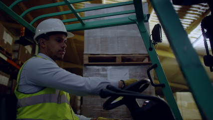 A forklift truck driver manoeuvring his truck around a warehouse