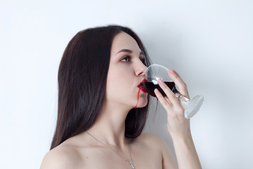 Woman with open eyes drinking wine, which runs on the lips