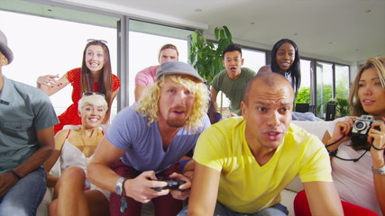 Happy group of friends socializing at home and playing video games