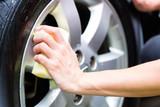 man cleaning wheel rim while car wash
