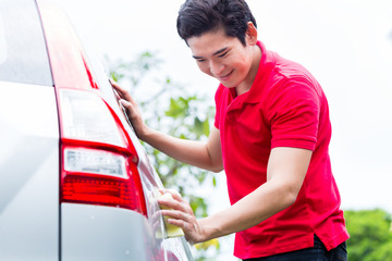 Asian man cleaning and washing car with sponge