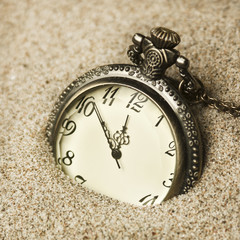 antique clock in the sand
