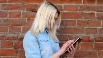 Young lady in blue denim shirt using tablet pc at brick wall