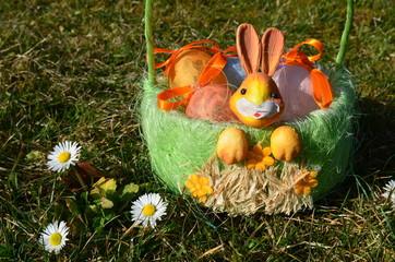 Osterkörbchen auf Wiese mit Gänseblümchen