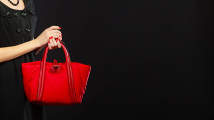 woman hand holds red handbag