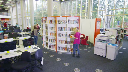 Diverse student group working in the library of large modern university building