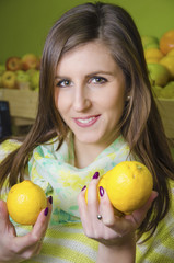 Young girl holding two lemons in greengrocery