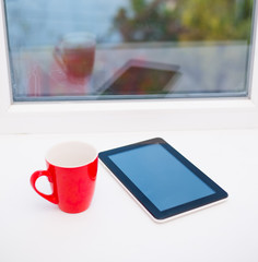 tablet and cup on the windowsill