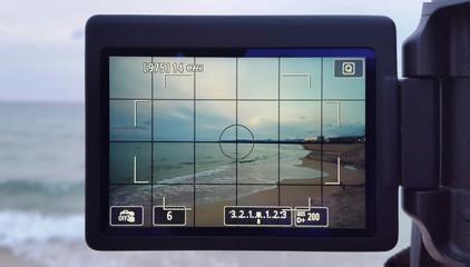 Visor de cámara digital haciendo una fotografía de una playa
