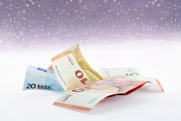 Falling snow and  euro banknotes
