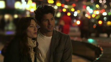 Attractive man and woman stand together beside a busy city road at night