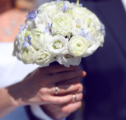 Closeup hands of bride and groom holding wedding white bouquet