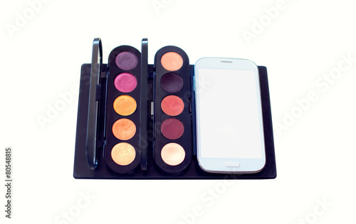 Palette of cosmetics and smartphone on a white background