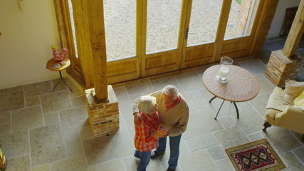 Cheerful romantic senior couple dance together at home
