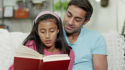 A father and his daughter spending time together at home, reading a book