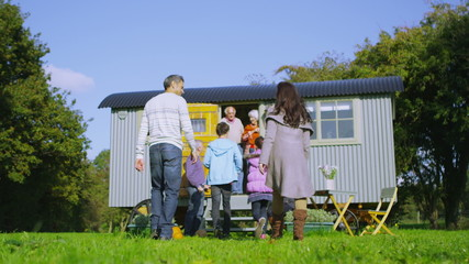 Happy extended family group relaxing outside quaint caravan in a natural setting